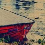 row boat tied to the side of the river